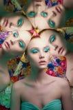 Mujer hermosa joven con maquillaje brillante del colorfull en fondo de la flor fotografía de archivo libre de regalías