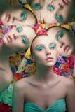 Mujer hermosa joven con maquillaje brillante del colorfull en fondo de la flor fotos de archivo