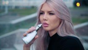 Mujer hermosa joven con maquillaje de la moda en el al aire libre con a con el vapor del cigarrillo electrónico 4k metrajes