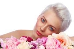 Mujer hermosa joven con maquillaje fresco y flores sobre blanco foto de archivo libre de regalías