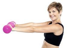 Mujer hermosa joven con pesas de gimnasia en manos Foto de archivo libre de regalías