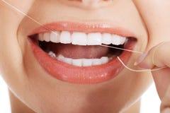 Mujer hermosa joven con seda dental. Imagen de archivo libre de regalías