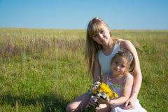 Mujer hermosa joven con su hija en un campo Fotos de archivo libres de regalías