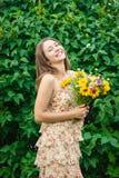 Mujer hermosa joven con un ramo de flores salvajes en un verano Foto de archivo libre de regalías