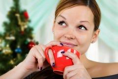 Mujer hermosa joven con una taza roja Imágenes de archivo libres de regalías