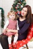 Mujer hermosa joven con usted hija cerca del árbol de navidad Foto de archivo libre de regalías
