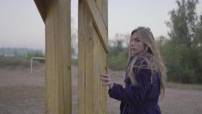 Mujer hermosa joven de la cámara lenta que camina a lo largo de la playa del otoño y que mira en la cámara almacen de metraje de vídeo