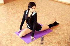 Mujer hermosa joven del ajuste que estira en la estera de la yoga Foto de archivo libre de regalías