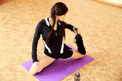 Mujer hermosa joven del ajuste que estira en la estera de la yoga Fotografía de archivo libre de regalías