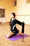 Mujer hermosa joven del ajuste que estira en la estera de la yoga Imagenes de archivo