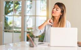 Mujer hermosa joven del estudiante con el ordenador portátil en la tabla, en casa imágenes de archivo libres de regalías