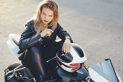 Mujer hermosa joven del motorista que se sienta en la presentación de la moto Imagen de archivo libre de regalías