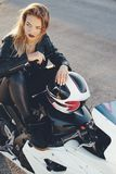 Mujer hermosa joven del motorista que se sienta en la presentación de la moto Imagenes de archivo