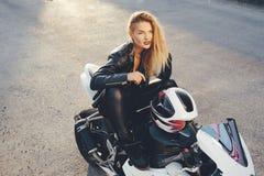 Mujer hermosa joven del motorista que se sienta en la presentación de la moto Fotografía de archivo