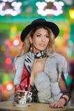 Mujer hermosa joven del pelo justo largo con el sombrero negro, la bufanda y el abrigo de pieles, tiro al aire libre en un día de Imagen de archivo