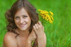 Mujer hermosa joven del retrato que sostiene el wildflower amarillo del ramo Foto de archivo libre de regalías
