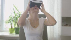 Mujer hermosa joven en auriculares de la realidad virtual que mira 360 grados de video Cantidad tirada en 4K almacen de video