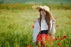 Mujer hermosa joven en campo de cereal con las amapolas Foto de archivo libre de regalías