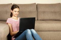 Mujer hermosa joven en casa que se sienta en el piso con el ordenador portátil Foto de archivo libre de regalías
