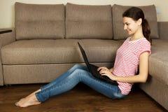 Mujer hermosa joven en casa que se sienta en el piso con el ordenador portátil Imagen de archivo libre de regalías