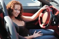 Mujer hermosa joven en coche deportivo fotos de archivo