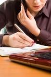 Mujer hermosa joven en el escritorio que escribe una nota. Fotos de archivo