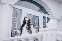 Mujer hermosa joven en el suéter que se coloca bajo nevadas imagen de archivo