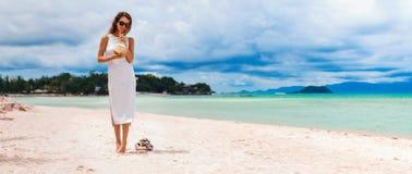 Mujer hermosa joven en el vestido, agua de consumición del coco en la playa tropical Imagenes de archivo