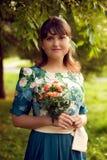 Mujer hermosa joven en el vestido de flores que presenta en parque con un bouq Fotos de archivo