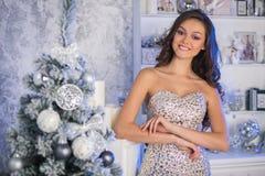 Mujer hermosa joven en el vestido elegante de plata que se coloca en interi Fotos de archivo