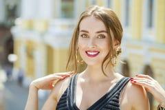 Mujer hermosa joven en el vestido negro que nos presenta al aire libre en soleado Imagen de archivo libre de regalías