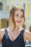 Mujer hermosa joven en el vestido negro que nos presenta al aire libre en soleado Imágenes de archivo libres de regalías
