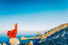 Mujer hermosa joven en el vestido rojo que mira al mar de las monta?as fotos de archivo libres de regalías
