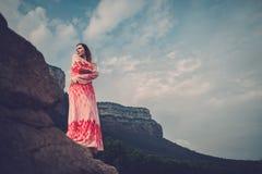 Mujer hermosa joven en el vestido rojo que mira en las montañas España, Sant Roma de Sau fotografía de archivo