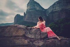 Mujer hermosa joven en el vestido rojo que mira en las montañas España, Sant Roma de Sau foto de archivo