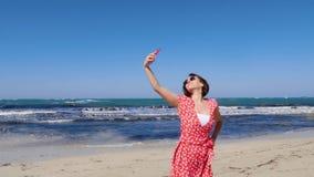 Mujer hermosa joven en el vestido rojo que toma el selfie con su teléfono de la cámara en la playa del mar con el fuerte viento y almacen de video