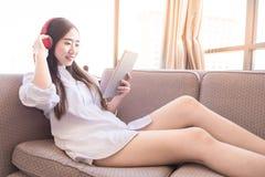 Mujer hermosa joven en equipo brillante que disfruta de la música en hea Fotos de archivo libres de regalías
