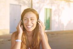 Mujer hermosa joven en equipo brillante que disfruta de música Fotos de archivo libres de regalías