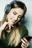 Mujer hermosa joven en equipo casual que disfruta de la música en casa Foto de archivo