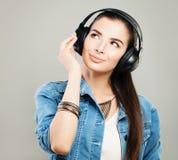 Mujer hermosa joven en equipo del dril de algodón que disfruta de la música Imagen de archivo