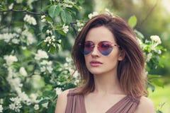 Mujer hermosa joven en gafas de sol al aire libre Muchacha linda con el pelo acodado marrón, retrato de la primavera imagen de archivo libre de regalías