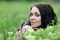 Mujer hermosa joven en hierba verde y flores Imagenes de archivo