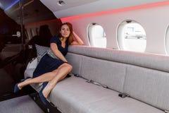 Mujer hermosa joven en interior de lujo en el jet del negocio Foto de archivo libre de regalías