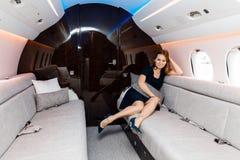Mujer hermosa joven en interior de lujo en el jet del negocio Foto de archivo
