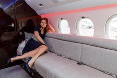 Mujer hermosa joven en interior de lujo en el jet del negocio Fotos de archivo libres de regalías