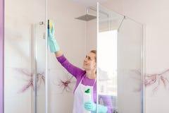 Mujer hermosa joven en la cabina blanca de la ducha de la limpieza del delantal fotografía de archivo