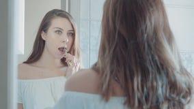 Mujer hermosa joven en la camisa que cepilla sus dientes en cuarto de baño Concepto de la belleza almacen de metraje de vídeo