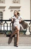 Mujer hermosa joven en la capa beige que presenta al aire libre en wea soleado Imagen de archivo libre de regalías