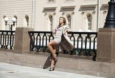 Mujer hermosa joven en la capa beige que presenta al aire libre en wea soleado Foto de archivo