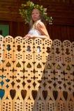 Mujer hermosa joven en la estancia blanca de la guirnalda del vestido y de la flor en el balcón decorativo de la casa del campo e foto de archivo libre de regalías